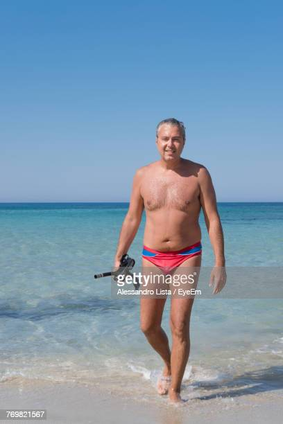 Portrait Of Shirtless Man With Scuba Mask Standing At Beach