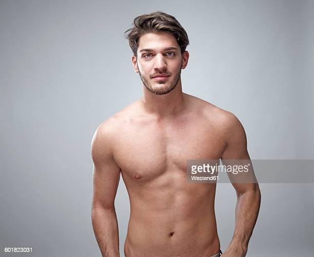 Portrait of shirtless young man in front of grey background