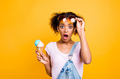 WTF! Portrait of shocked frustrated girl looking out eyeglasses with wide open eyes mouth having ice cream in waffle cone isolated on yellow background