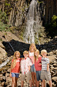 Portrait of siblings in front of waterfall