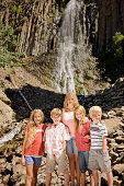 Portrait of siblings in front of waterfall