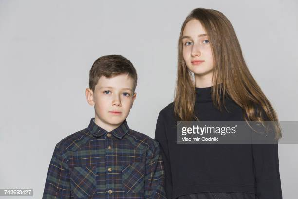 Portrait of siblings standing against white background