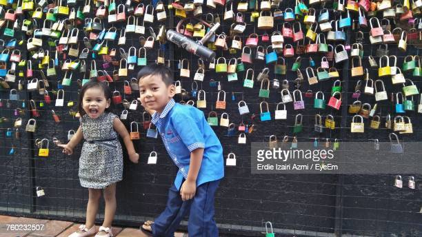 Portrait Of Siblings Standing By Colorful Love Locks Hanging On Metal Grate