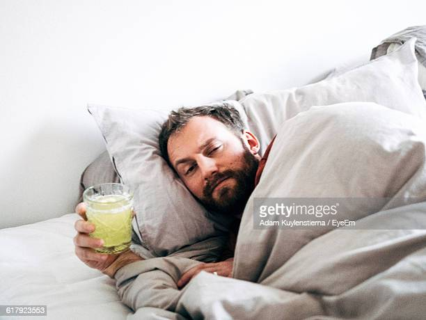Portrait Of Sick Man Holding Drink While Lying On Bed At Home