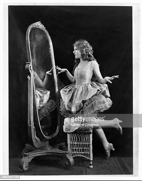 Portrait of silent film actress Mary Pickford looking in a fulllength mirror 1920