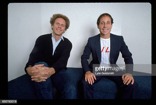 Portrait of Simon and Garfunkel They are shown waistup sitting on the floor next to a white wall Photograph 1981