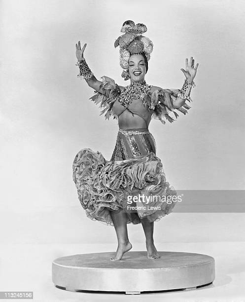 Portrait of singer and actress Carmen Miranda wearing an elaborate headdress and costume in the 1940's