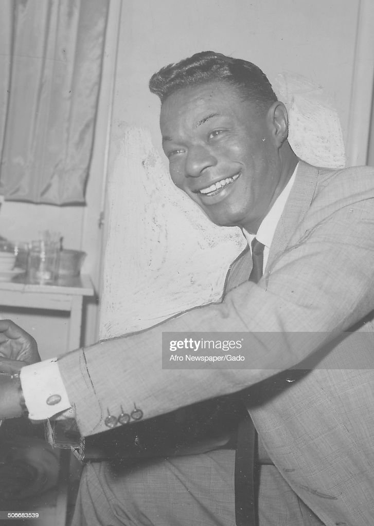 Portrait of singer and Jazz musician <a gi-track='captionPersonalityLinkClicked' href=/galleries/search?phrase=Nat+King+Cole&family=editorial&specificpeople=217991 ng-click='$event.stopPropagation()'>Nat King Cole</a> smiling and playing an instrument, 1950.