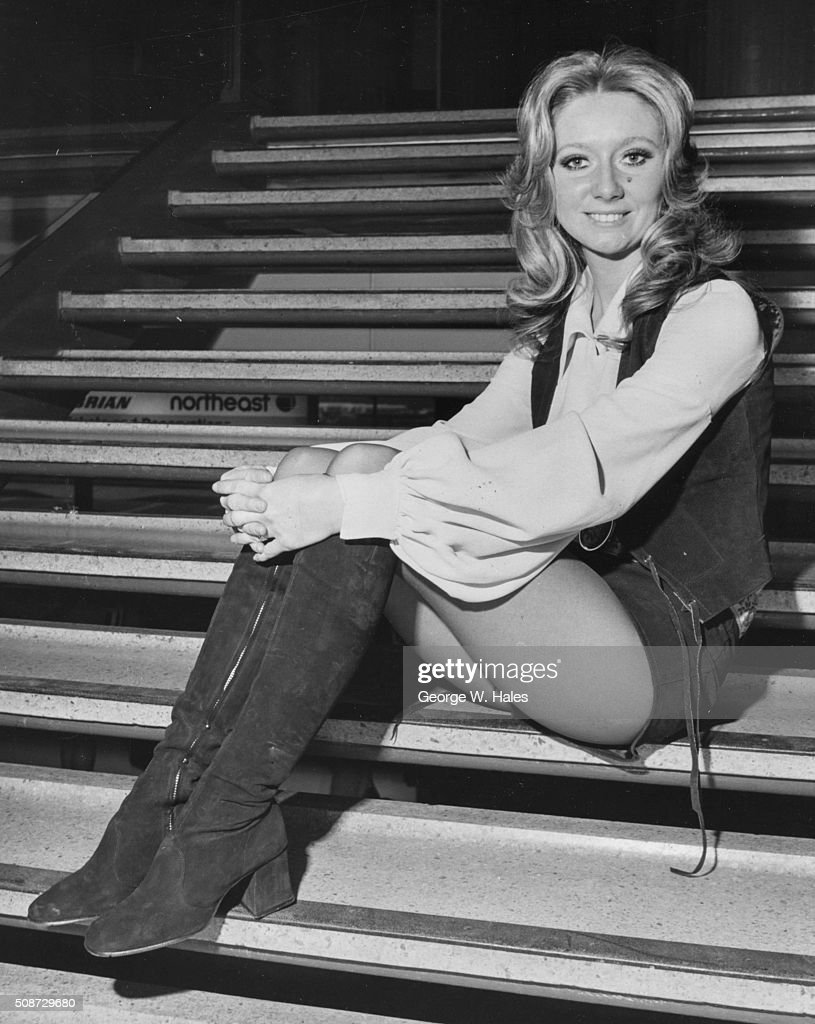 Portrait of singer Clodagh Rodgers sitting on a staircase at Heathrow Airport wearing kneehigh boots and hot pants preparing to depart to compete in...