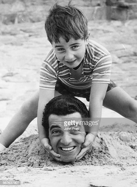Portrait of singer Frankie Vaughan is buried in the sand as his son David jokes around with his head on a beach in Jersey August 3rd 1959
