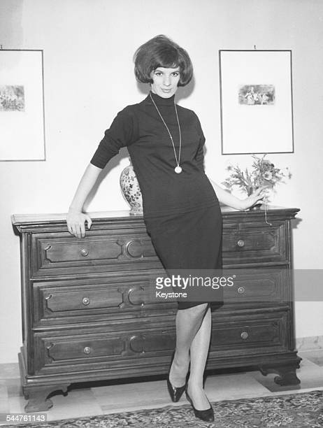 Portrait of singer Iva Zanicchi standing in front of a set of drawers circa 1965