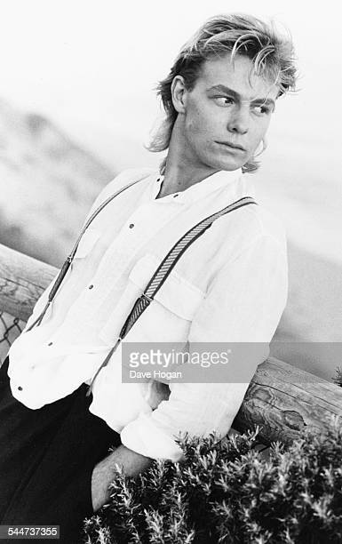 Portrait of singer Jason Donovan leaning against a wooden fence circa 1988