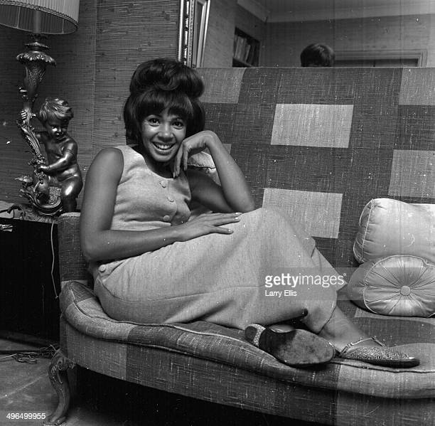 Portrait of singer Shirley Bassey sitting on a couch September 14th 1964
