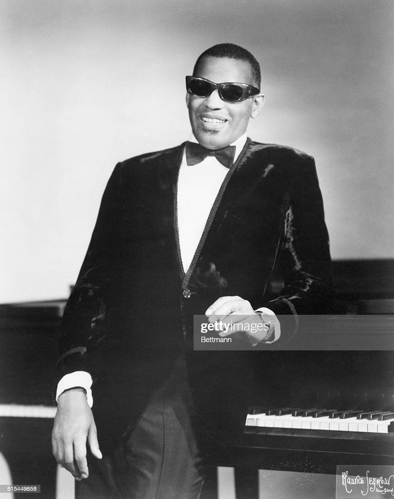 Portrait of singer/composer Ray Charles standing by his piano.