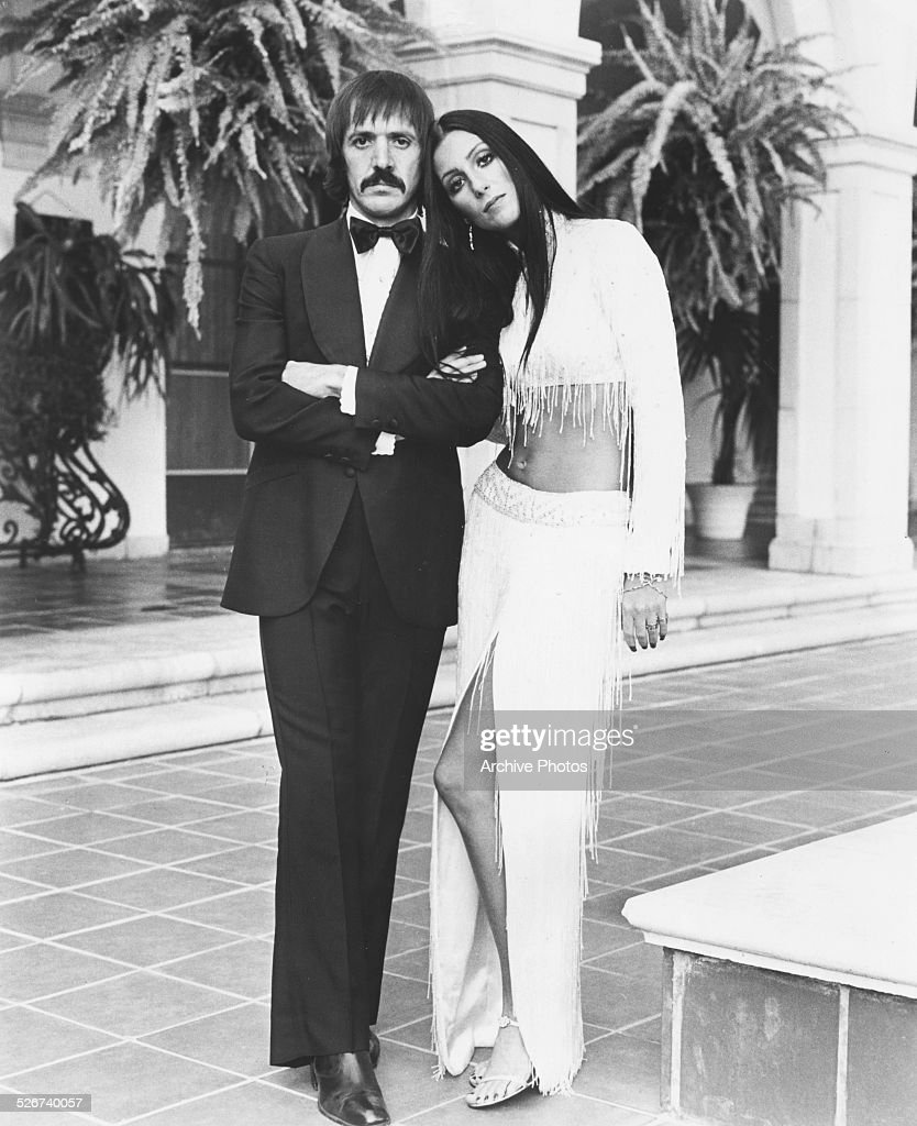 Portrait of singing duo Sonny Bono and Cher wearing formal dress on an outdoor patio circa 1975