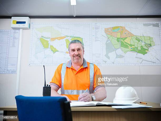 Portrait of site manager working at desk in opencast coalmine