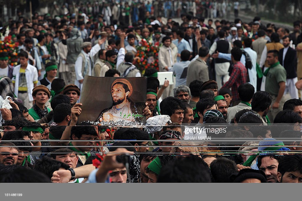 A portrait of slain Afghan national hero Ahmad Shah Massoud is pictured during a ceremony marking the eleventh anniversary of his death in Kabul on September 8, 2012. Massoud, nicknamed the 'Lion of the Panjshir' for his armed struggle against the Taliban that ruled Afghanistan at the time, died September 9, 2001 when two Tunisians posing as journalists with fake Belgian passports detonated a bomb hidden in the camera as they pretended to interview him. His death, just two days before the September 11 attacks in New York and Washington, has been linked to Osama bin Laden's al-Qaeda network by US officials. AFP PHOTO/ SHAH Marai