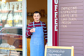 Portrait of small business coffee shop owner smiling and standing in front of shop serving a takeaway coffee, Successful young man working in trendy cafe store holding delicious cup of coffee