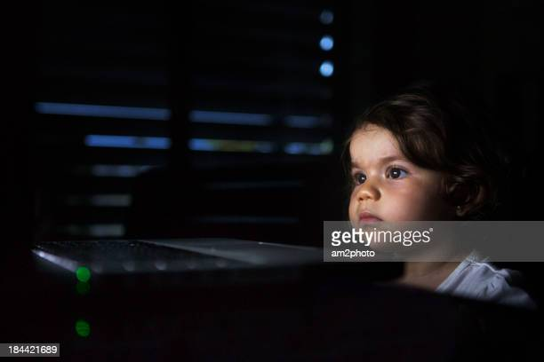 Portrait of small girl looking the laptop in the d
