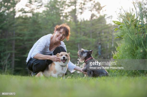 Portrait of smiling Adult Woman outdoors with her Corgi and Mini Schnauzer Dogs
