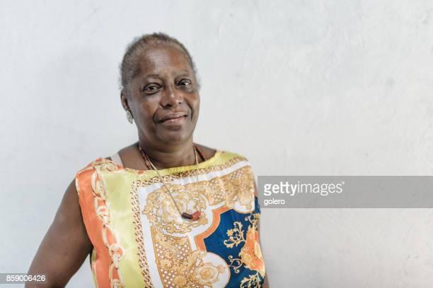 Porträt von lächelnden Afro-brasilianische senior Frau vor weißer Wand