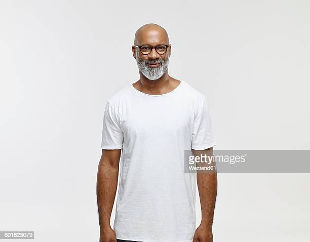 Portrait of smiling bald man with beard wearing spectacles and white t-shirt