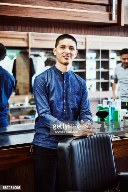 Portrait of smiling barber standing next to chair in barber shop