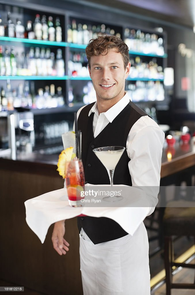 Portrait Of Smiling Bartender Holding Tray With Cocktails ...  Portrait Of Smi...