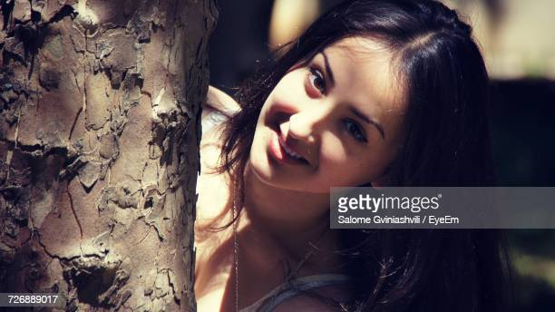 Portrait Of Smiling Beautiful Woman By Tree Trunk