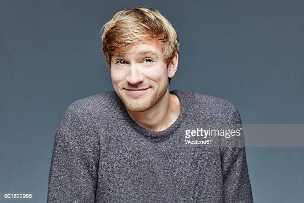 Portrait of smiling blond man in front of grey background
