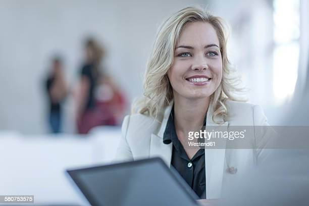 Portrait of smiling blond woman face to face with a business partner