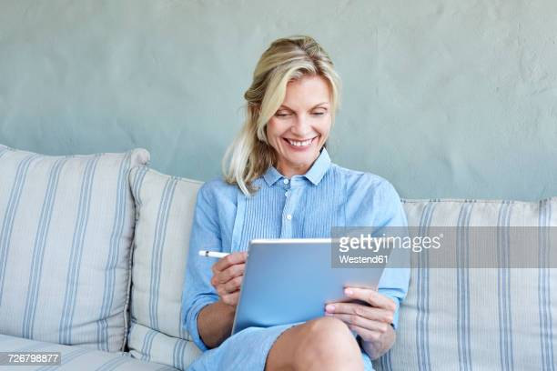 Portrait of smiling blond woman sitting on couch looking at tablet