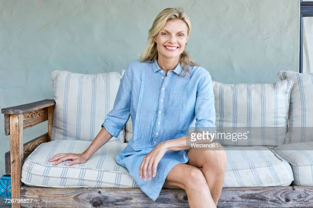 Portrait of smiling blond woman sitting on couch