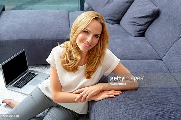Portrait of smiling blond woman sitting on floor with laptop near a couch in living room