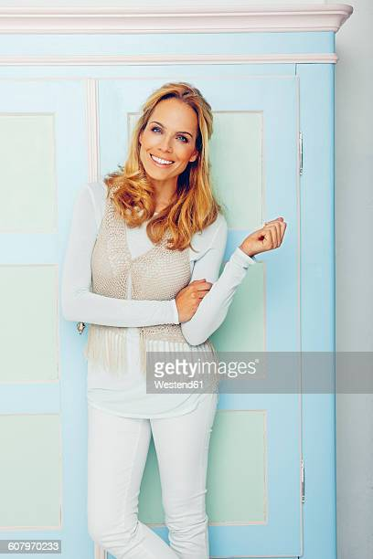 Portrait of smiling blond woman standing in front of wardrobe
