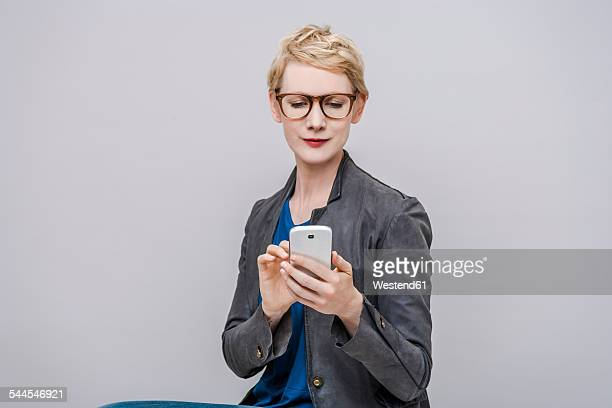 Portrait of smiling blond woman using smartphone in front of grey background