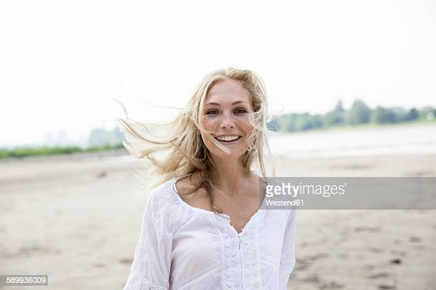 Portrait of smiling blond woman with blowing hait on a beach