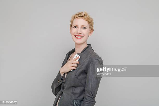 Portrait of smiling blond woman with smartphone in front of grey background