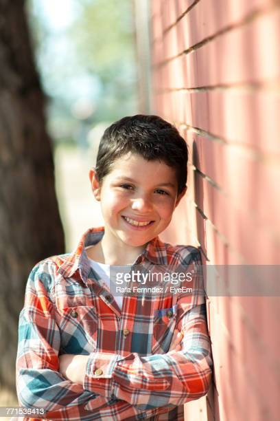 Portrait Of Smiling Boy Leaning On Brick Wall