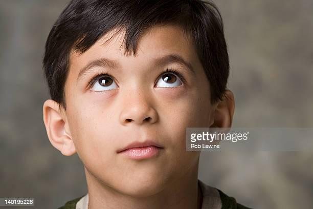 Portrait of smiling boy (8-9) looking up, studio shot