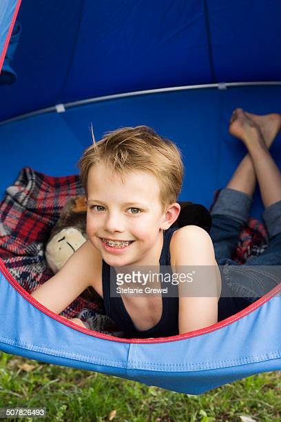 Portrait of smiling boy lying in tent suspended above grass