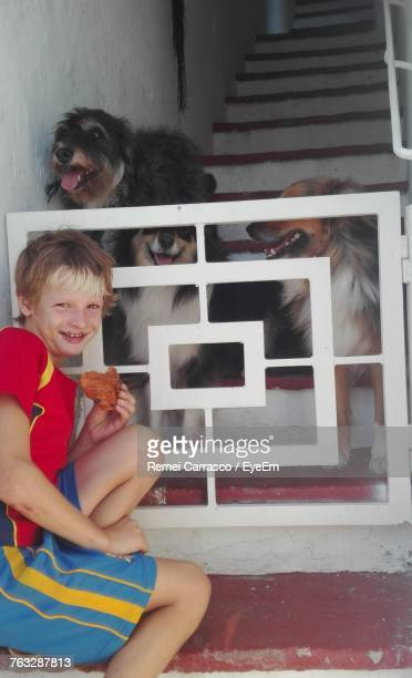 Portrait Of Smiling Boy Sitting With Food By Dogs