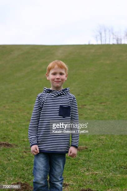 Portrait Of Smiling Boy Standing On Grassy Field Against Sky