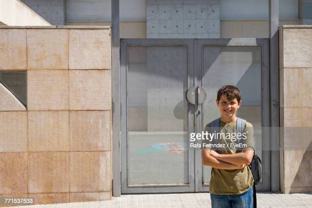 Portrait Of Smiling Boy With Backpack Standing Against Metal Door During Sunny Day