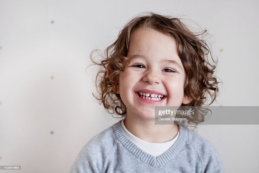 Portrait of smiling boy with curly brown hair : Stock Photo