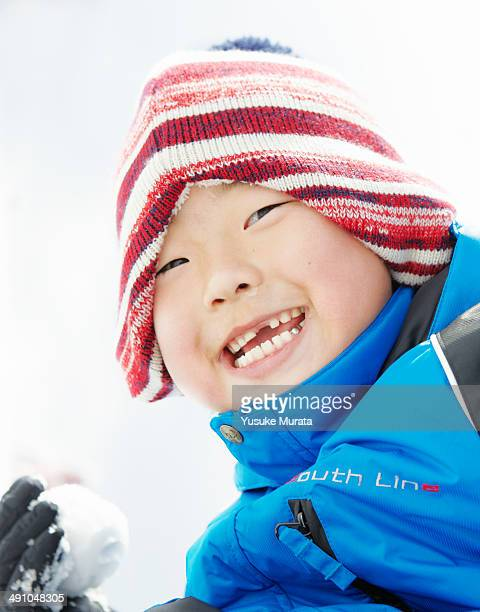 Portrait of smiling boy with snow ball