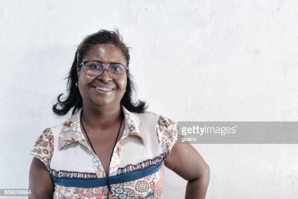 Porträt des Lächelns brasilianischen Mitte Erwachsene Frau vor weißer Wand