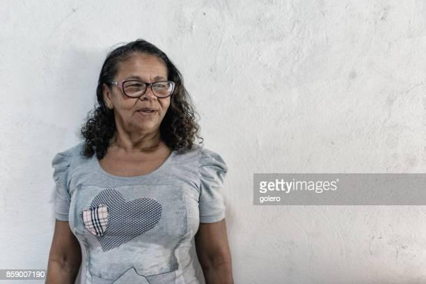 Porträt von lächelnden senior Brasilianerin vor weißer Wand