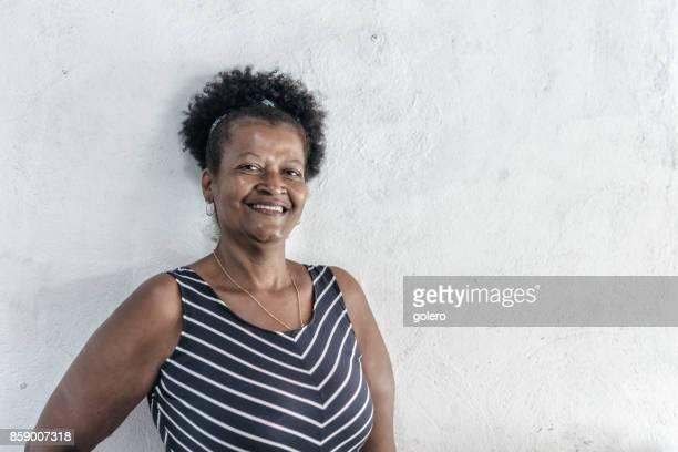 Porträt von lächelnden Brasilianerin vor weißer Wand