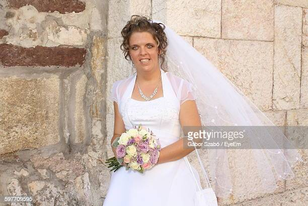 Portrait Of Smiling Bride Holding Flower Bouquet While Standing Against Wall